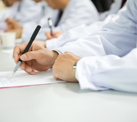 Group of doctors writing at a conference.