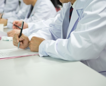 asian medical: Group of doctors writing at a conference.