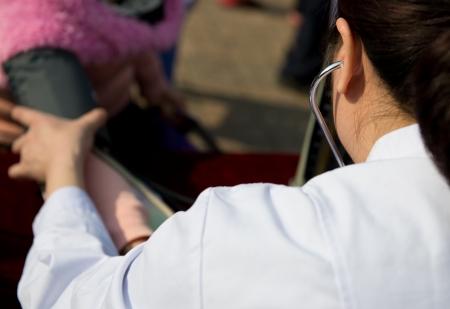 consulta médica: Médico medición de la presión arterial de las personas en la consulta médica. Foto de archivo
