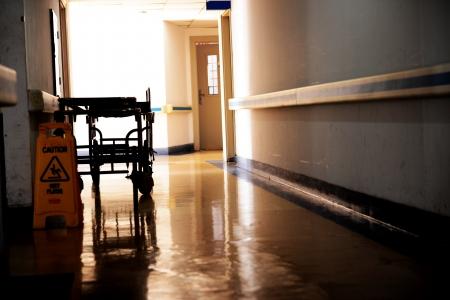 wet floor: hallway in hospital with bed.