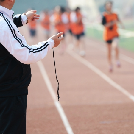 Close-up of a man holding a stopwatch to measure performances of the runners in a stadium  photo