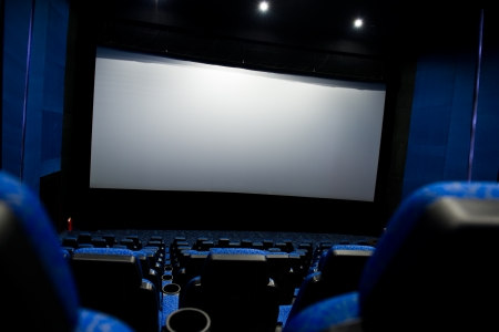 Dark movie theatre interior. screen and chairs.