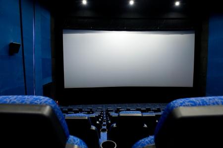 home cinema: Dark movie theatre interior. screen and chairs.