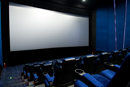 oscar: Dark movie theatre interior. screen and chairs.