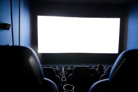 Dark movie theatre interior. screen and chairs.