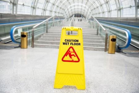Wet floor caution sign on hotel corridor floor.