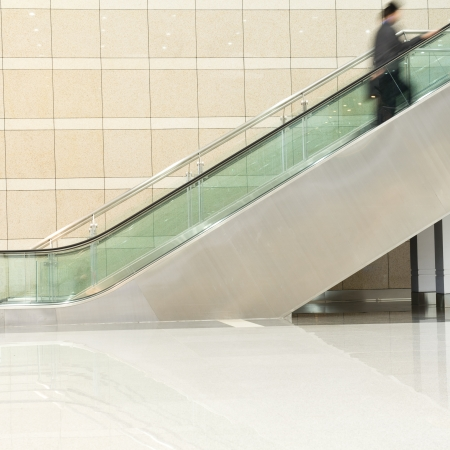 Business people on escalator. Blurred motion photo