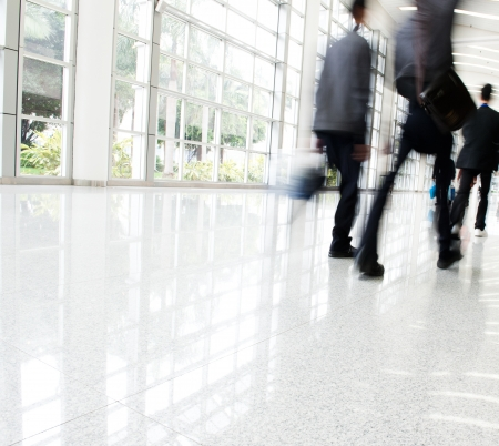 building glass: Business people rushing in the lobby. motion blur
