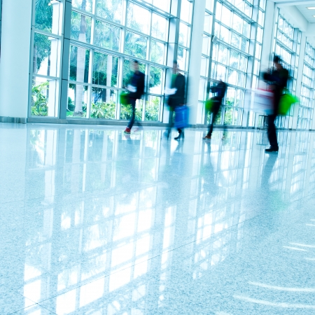 businesslike: Business people rushing in the lobby. motion blur