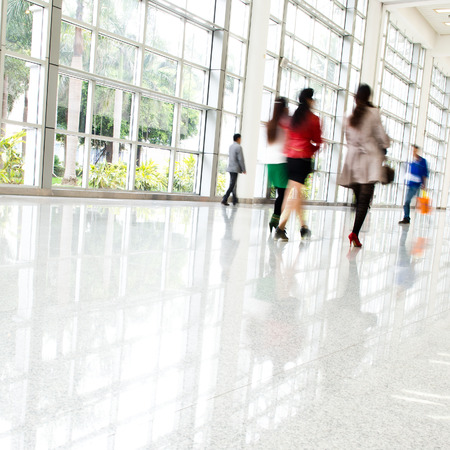 blurred people: Business people rushing in the lobby. motion blur
