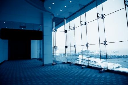 blue carpet: empty long corridor in the modern office building.