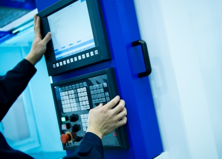 worker working with cnc machine at workshop. Stock Photo - 23534246