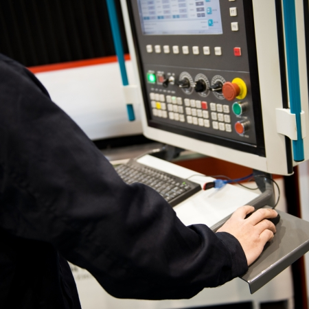 worker working with cnc machine at workshop. photo