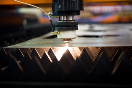 laser cutting: Industrial laser cutter with sparks.