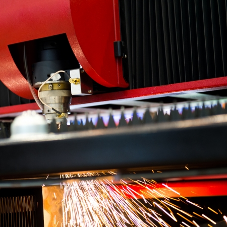 precise: Industrial laser cutter with sparks.