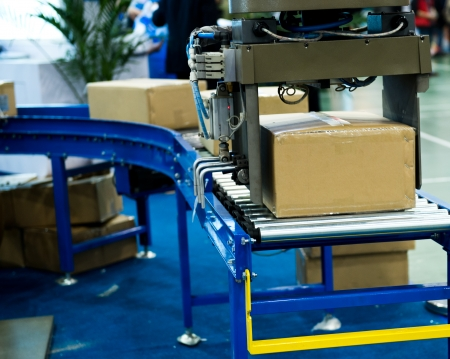 produce sections: package boxes on industrial conveyor line.