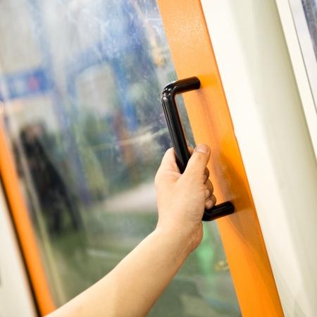 door knob: worker open the door of cnc machine at workshop.