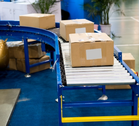 transporting: package boxes on industrial conveyor line.