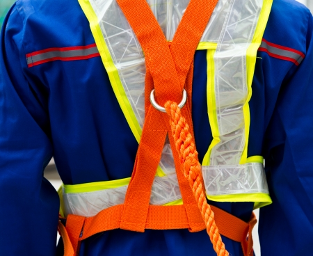 safety harness: construction site worker with safety rope.
