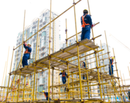 scaffold: Construction workers working on scaffolding