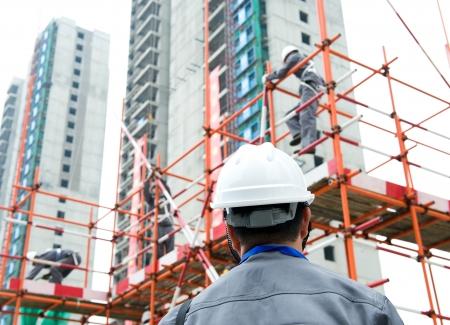 Vue arrière de constructeur le contrôle d'un chantier de construction inspecteur travaille. Banque d'images - 23700790
