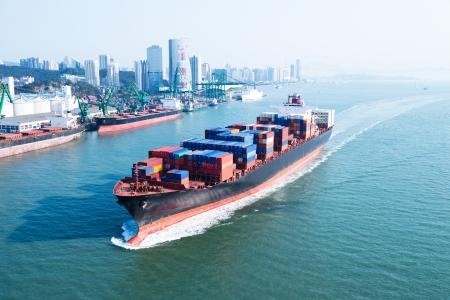 送料: 大型コンテナー船が港に到着します。 写真素材