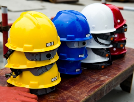 workplace safety: Some construction helmets on work place. Stock Photo