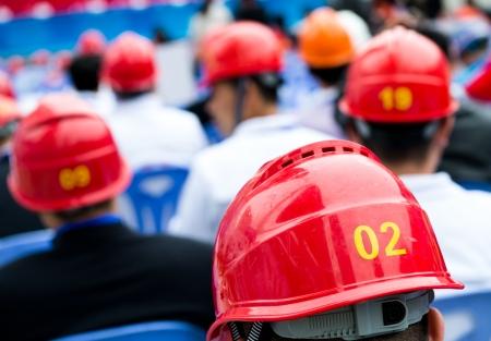 casco rojo: Vista posterior de muchos trabajadores de la construcción con el casco.