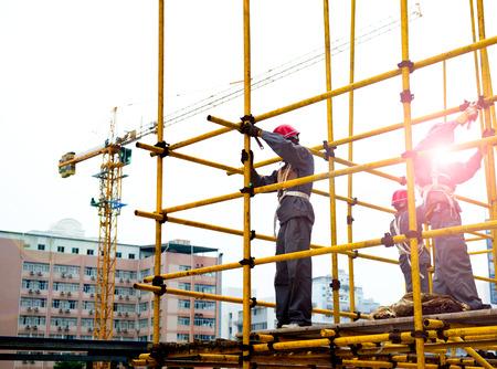 Trabajadores de la construcción que trabajan en andamios