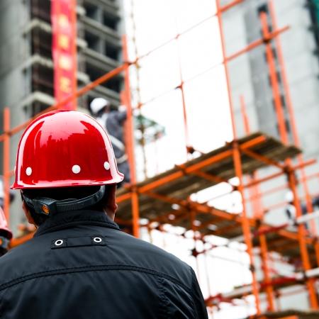 casco rojo: Vista posterior del constructor de inspector de control de las obras de construcción de un sitio.