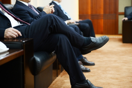 crossed legs: Businessman talking to each other at a meeting.