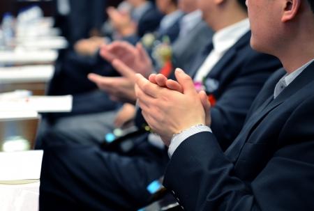 Zakenmensen handen applaudisseren tijdens vergadering. Stockfoto