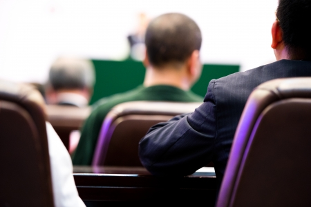 Rear view of business people listening attentively at conference. photo