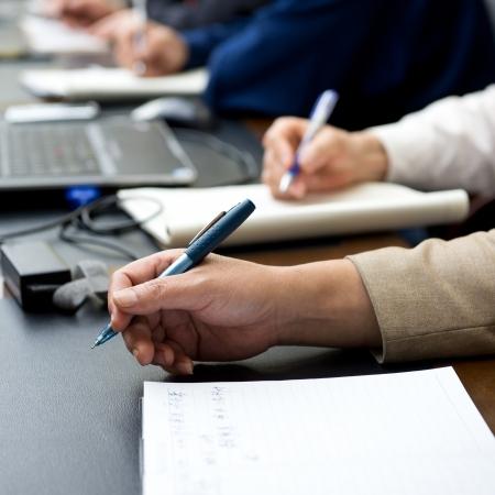 Closeup of human hand writing at a conference. photo