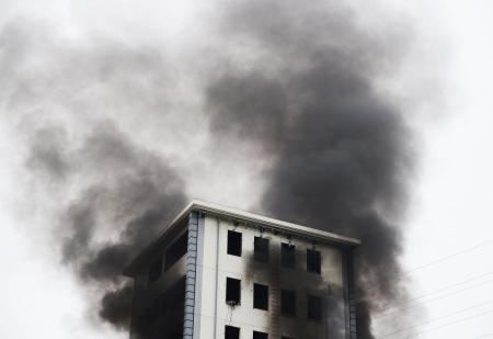 incendio casa: La quema de fuego y humo negro sobre el edificio de gran altura. Editorial