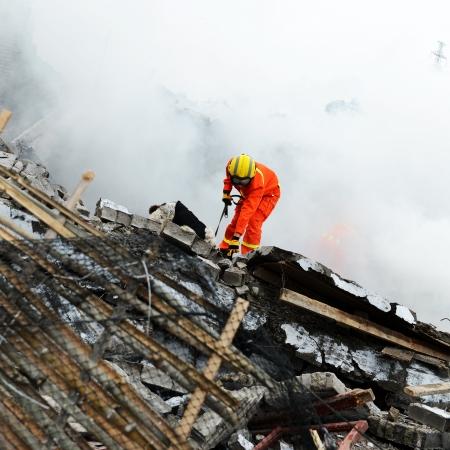 수색 구조 대원은 구조견의 도움을 받아 파괴 된 건물을 수색합니다.