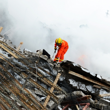 house fire: Search and rescue forces search through a destroyed building with the help of rescue dogs.  Stock Photo
