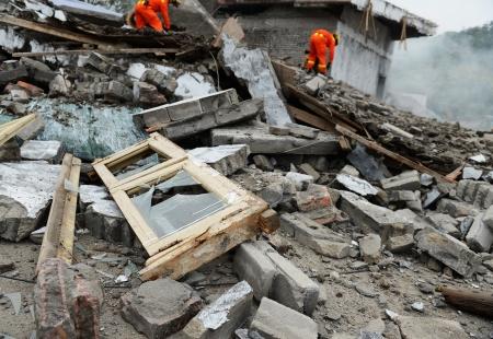 Búsqueda y rescate buscan a través de las fuerzas de un edificio destruido. Foto de archivo