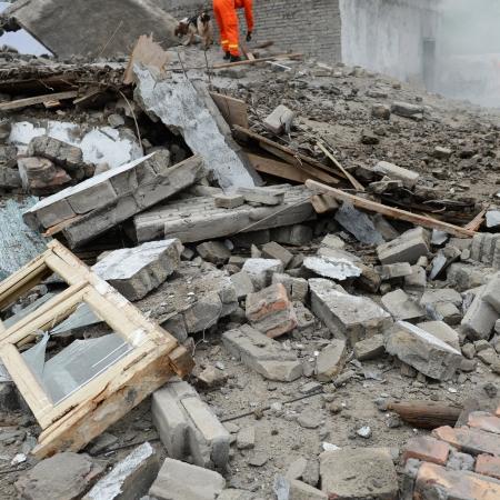 derrumbe: Búsqueda y rescate buscan a través de las fuerzas de un edificio destruido.