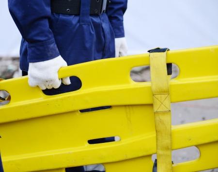 emergency stretcher: Plastic rescue stretcher in hand.
