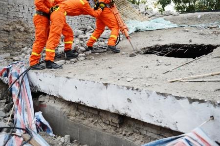 Zoek-en reddingsacties krachten biedt een verwoest gebouw.