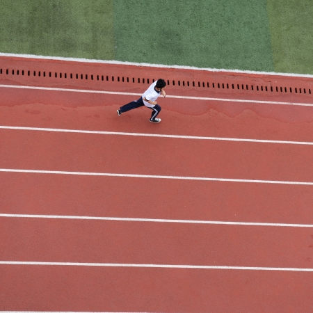 Top view of young student running on track. photo