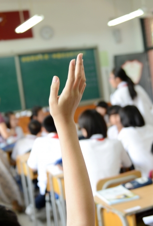 Raised hands in class of middle school.