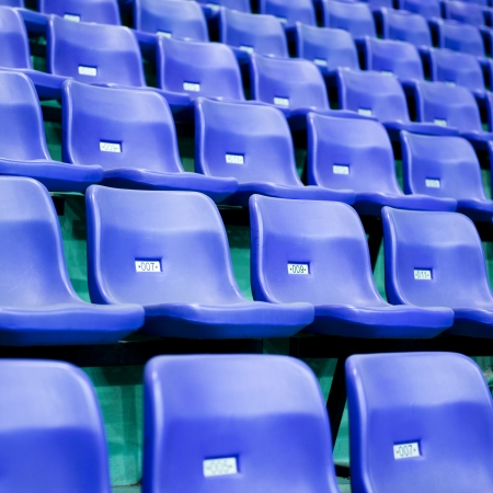sports venue: Rows of blue stadium seats with numbers.