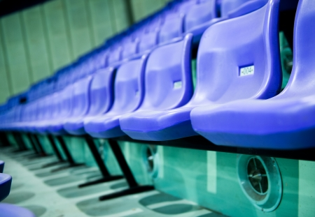 sports hall: Rows of blue stadium seats with numbers.