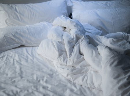 bed sheet: close up of messy bedding sheets and pillow Stock Photo