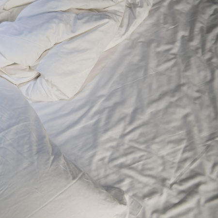 close up of messy bedding sheets and pillow photo