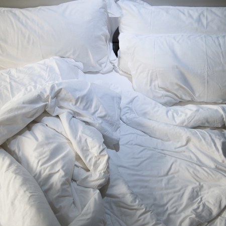 unmade: close up of messy bedding sheets and pillow Stock Photo