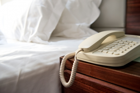 hotel: Phone on a table near a bed. Stock Photo