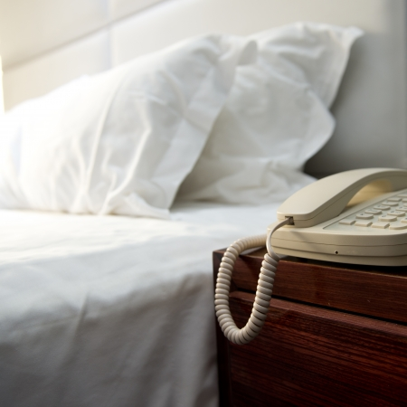 Phone on a table near a bed. photo